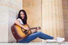 Mujer sonriente hermosa que toca la guitarra acústica Foto de archivo