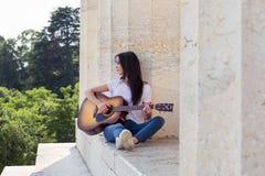 Mujer sonriente hermosa que toca la guitarra acústica Imagen de archivo libre de regalías