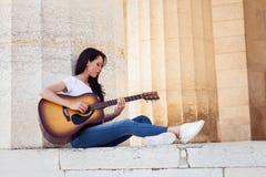 Mujer sonriente hermosa que toca la guitarra acústica Imagenes de archivo