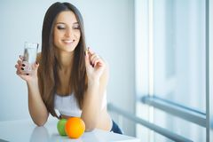 Mujer sonriente hermosa que toma la píldora de la vitamina Suplemento dietético foto de archivo