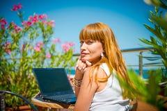 Mujer sonriente hermosa que trabaja en el ordenador portátil fotografía de archivo libre de regalías
