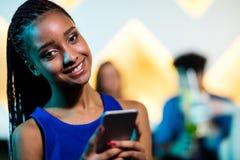 Mujer sonriente hermosa que usa el teléfono móvil Foto de archivo