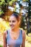 Mujer sonriente iluminada por un rayo de sol fotografía de archivo libre de regalías