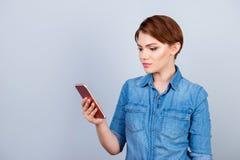 Mujer sonriente joven aislada en SMS gris de la lectura de fondo en h Imagen de archivo libre de regalías