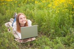 Mujer sonriente joven con el cuaderno en el parque que mira el ordenador portátil Imagenes de archivo