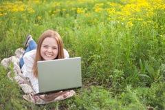 Mujer sonriente joven con el cuaderno en el parque que mira el ordenador portátil Imagen de archivo