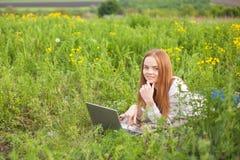 Mujer sonriente joven con el cuaderno en el parque que mira el ordenador portátil Imagen de archivo libre de regalías