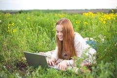 Mujer sonriente joven con el cuaderno en el parque que mira el ordenador portátil Fotos de archivo libres de regalías