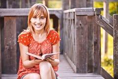 Mujer sonriente joven con el libro Fotografía de archivo