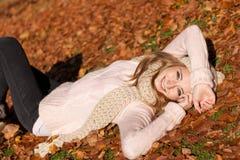 Mujer sonriente joven con el sombrero y la bufanda al aire libre en otoño Foto de archivo libre de regalías