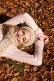 Mujer sonriente joven con el sombrero y la bufanda al aire libre en otoño imagenes de archivo