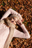 Mujer sonriente joven con el sombrero y la bufanda al aire libre en otoño Imagen de archivo