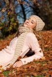 Mujer sonriente joven con el sombrero y la bufanda al aire libre en otoño Foto de archivo