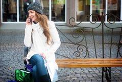 Mujer sonriente joven con el teléfono móvil imágenes de archivo libres de regalías
