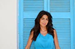 Mujer sonriente joven con el vestido azul en un obturador azul de madera fotos de archivo