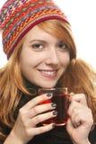 Mujer sonriente joven con ingenio del calentamiento del casquillo del invierno Imagenes de archivo