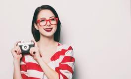 Mujer sonriente joven con la cámara retra Fotos de archivo libres de regalías