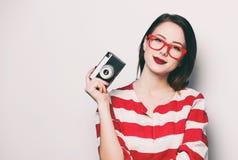 Mujer sonriente joven con la cámara retra Imagenes de archivo