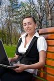 Mujer sonriente joven con la computadora portátil Fotografía de archivo