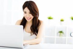 Mujer sonriente joven con la computadora portátil Imagen de archivo libre de regalías