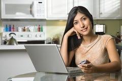 Mujer sonriente joven con la computadora portátil y el teléfono celular Fotografía de archivo libre de regalías