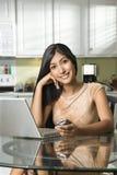 Mujer sonriente joven con la computadora portátil y el teléfono celular Fotos de archivo