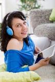 Mujer sonriente joven con la tableta   y auriculares en casa Fotos de archivo