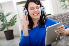 Mujer sonriente joven con la tableta y los auriculares en casa Fotografía de archivo libre de regalías