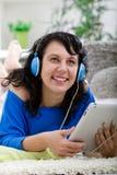 Mujer sonriente joven con la tableta y los auriculares en casa Imagenes de archivo