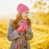 Mujer sonriente joven con la taza de café en manos que disfruta de otoño Foto de archivo libre de regalías
