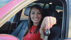Mujer sonriente joven con llaves en su nuevo coche almacen de metraje de vídeo