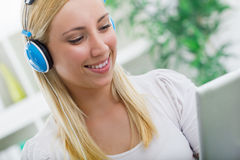 Mujer sonriente joven con los auriculares en casa Fotografía de archivo