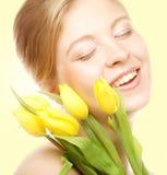 Mujer sonriente joven con los tulipanes amarillos Fotos de archivo