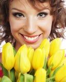 Mujer sonriente joven con los tulipanes amarillos Fotos de archivo libres de regalías