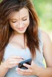 Mujer sonriente joven con smartphone Imagen de archivo