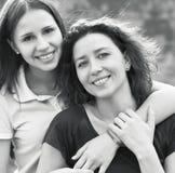 Mujer sonriente joven con su hija adolescente al aire libre Imagen de archivo libre de regalías