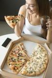 Mujer sonriente joven con una rebanada de pizza Fotos de archivo
