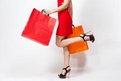 Mujer sonriente joven de moda caucásica del encanto atractivo en el vestido rojo aislado en el fondo blanco Copie el anuncio del  imagen de archivo