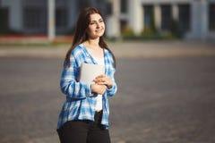 Mujer sonriente joven del estudiante con los libros en las manos que se colocan al aire libre Imagenes de archivo