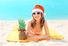 Mujer sonriente joven del retrato de la Navidad en el sombrero rojo y la piña de santa que mienten en la playa sobre el mar Foto de archivo