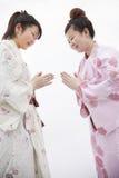 Mujer sonriente joven dos en kimonos japoneses que arquea el uno al otro, tiro del estudio Fotografía de archivo libre de regalías