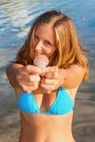 Mujer sonriente joven en control del bikini en cáscara del mar de las manos Imagenes de archivo
