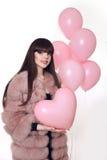 Mujer sonriente joven en el abrigo de pieles de la moda que aplaza el corazón rosado Fotografía de archivo