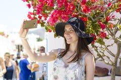 Mujer sonriente joven en el sombrero que toma un selfie el vacaciones Imagen de archivo
