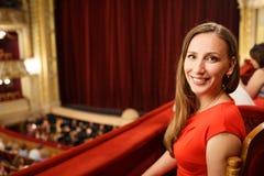 Mujer sonriente joven en el vestido que se sienta en teatro imágenes de archivo libres de regalías