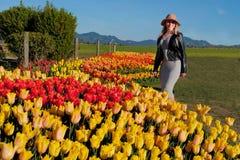 Mujer sonriente joven en jardín por las camas de tulipán Imagen de archivo libre de regalías