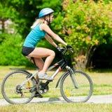Mujer sonriente joven en la bici Imagenes de archivo
