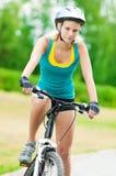 Mujer sonriente joven en la bici Foto de archivo libre de regalías