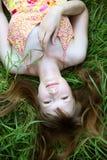 Mujer sonriente joven en la hierba Imágenes de archivo libres de regalías