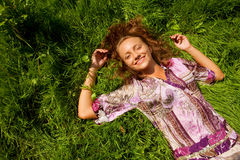 Mujer sonriente joven en la hierba Imagen de archivo libre de regalías